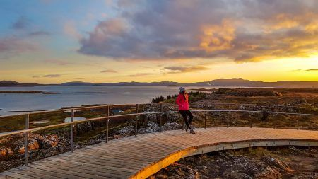 A beautiful girl wearing a pink jacket, leaning on a barrier during the sunset over national park Þingvellir in Iceland.
