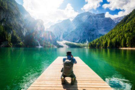 Travel hiker taking photo of Lake Braies (Lago di Braies) in Dolomites Mountains, Italy