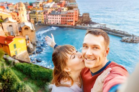 Vernazza, national park Cinque Terre, Liguria, Italy, Europe. Tourists happy couple taking selfie photo on camera.
