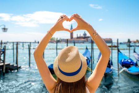 Woman having heart shape with hands on beautiful view of Venice