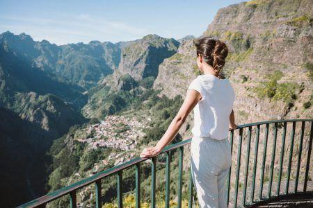 Girl at Viewpoint Eira do Serrado looking to Curral das Freiras village in the Nuns Valley in beautiful mountain scenery, municipality of Câmara de Lobos, Madeira island, Portugal.