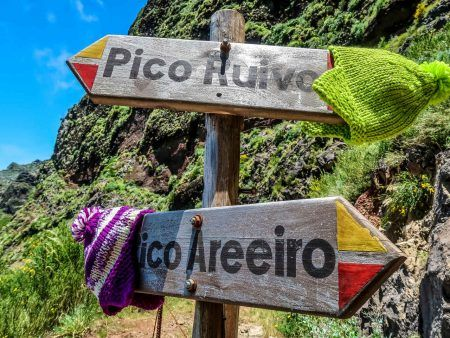 Signboard on the touristic trail Pico Ruivo- Pico Areeiro with two warm hats on it. Madeira. Portugal.